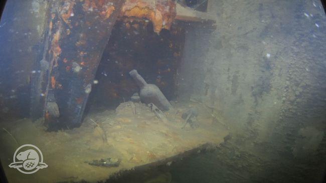 Des bouteilles et d'autres artefacts sur une étagère dans une cabine sur le pont inférieur du Terror. © Parcs Canada, Équipe d'archéologie subaquatique