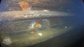 Des assiettes et d'autres artefacts sur des étagères près d'une table où des membres d'équipage de rang inférieur auraient mangé leur repas. © Parcs Canada, Équipe d'archéologie subaquatique