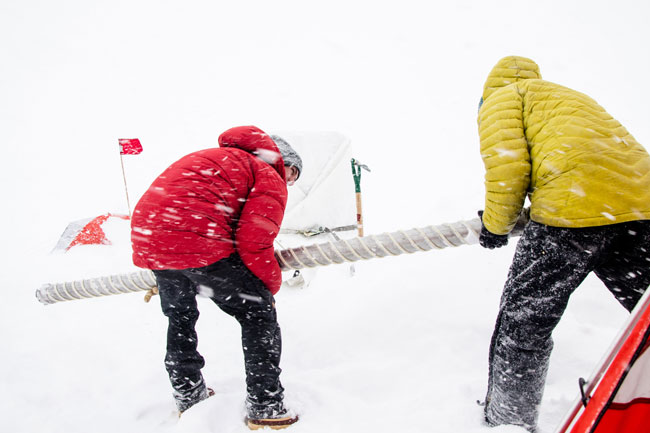 Récupération d'une section de carotte de glace pendant une tempête de neige à l'ouest du Groenland ©Sarah Das - WHOI